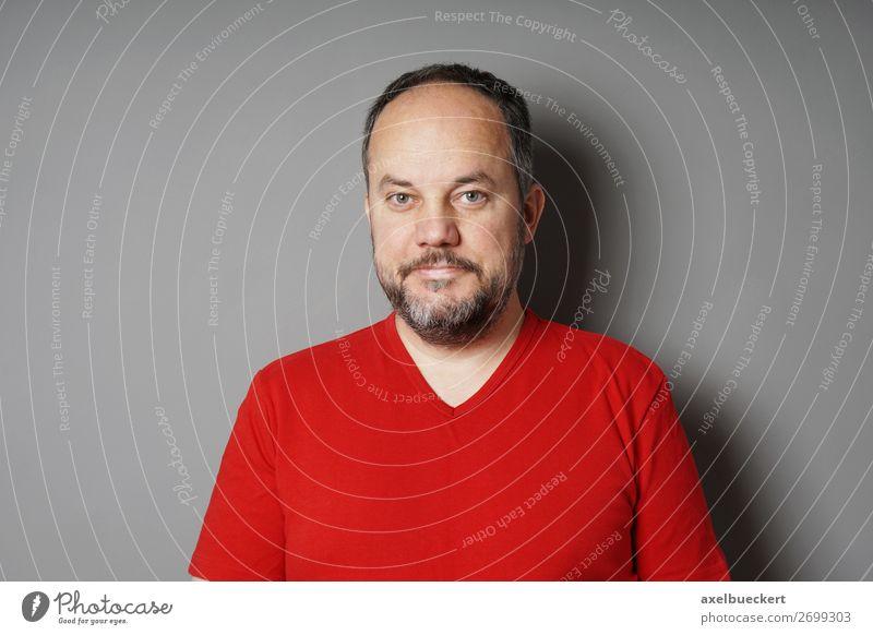 Mann Ende 40 Mensch maskulin Erwachsene 1 30-45 Jahre 45-60 Jahre Mauer Wand T-Shirt schwarzhaarig grauhaarig kurzhaarig Vollbart Lächeln grinsen rot Farbfoto