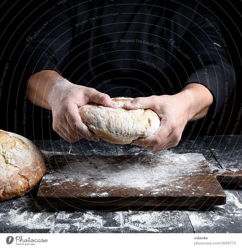 männliche Kochhände halten einen ganzen Laib gebackenes Rundbrot. Brot Ernährung Tisch Küche Mensch Hand machen dunkel frisch braun schwarz weiß Tradition