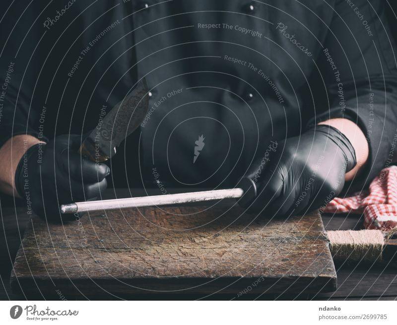 Koch in schwarzen Latexhandschuhen schärft ein Messer Küche Restaurant Beruf Mensch Mann Erwachsene Hand Handschuhe Stahl retro braun weiß Klinge Holzplatte