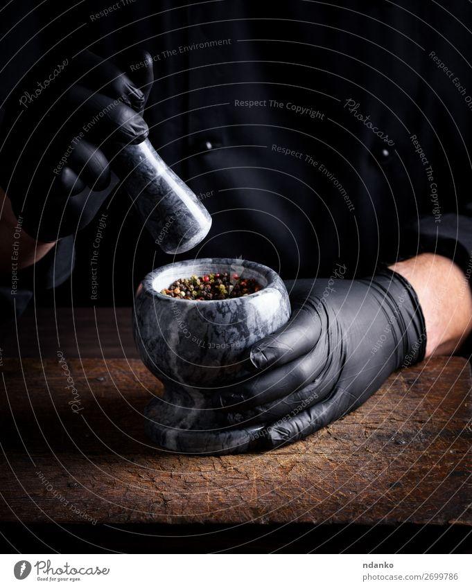 Koch in schwarzen Latexhandschuhen hält einen Steinmörser. Kräuter & Gewürze Tisch Küche Arbeit & Erwerbstätigkeit Werkzeug Mensch Mann Erwachsene Hand