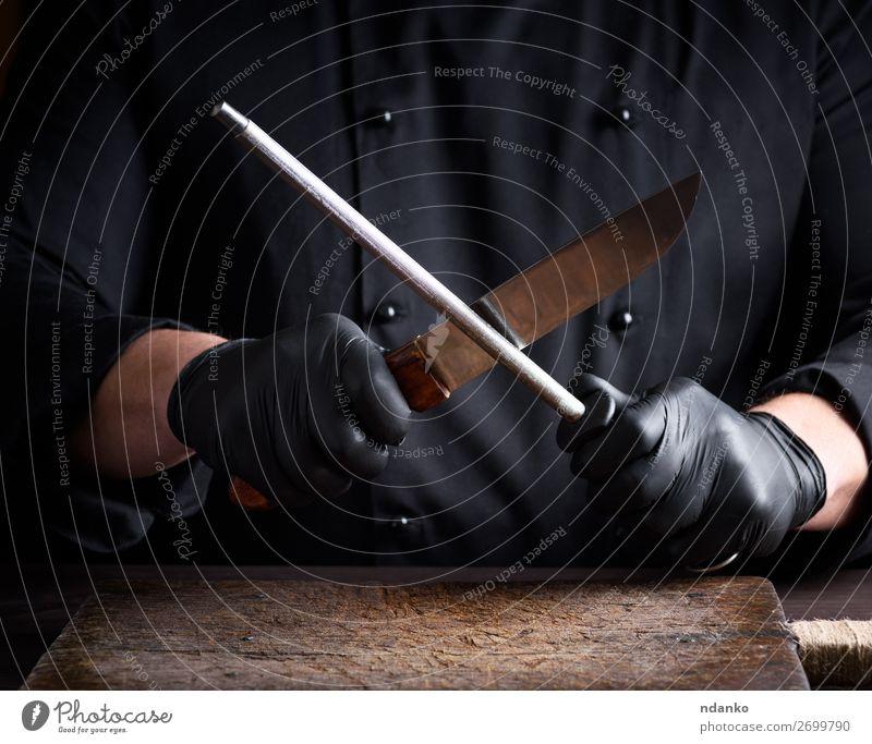 Koch in schwarzen Latexhandschuhen schärft ein Messer Küche Restaurant Beruf Mensch Mann Erwachsene Hand Handschuhe Stahl sitzen Küchenchef Holzplatte
