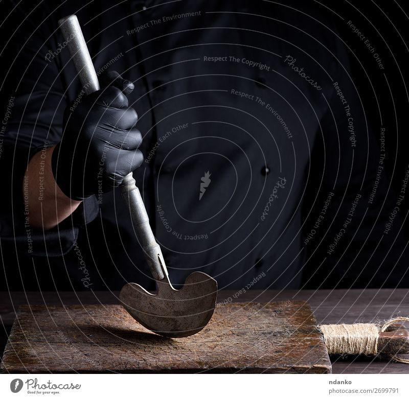 Koch in schwarzer Kleidung hält in der Hand ein altes Metallmesser. Messer Küche Beruf Handschuhe Stahl weiß Holzplatte Hackmesser Metzger Küchenchef Halt