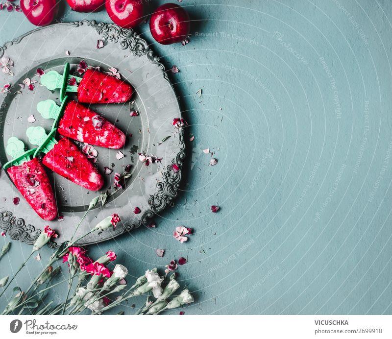 Obst und Beeren Eis am Stiel . Hausgemachtes Eis im Vintage-Teller auf blauem Küchentisch im Hintergrund mit Sommerblumen, Ansicht von oben. Gesunde Sommerdesserts. Gefrorene Säfte am Stiel. Veganes Eis