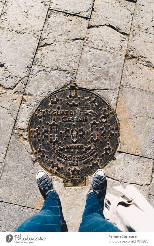 Woman stands on manhole cover in Cascais Mensch Ferien & Urlaub & Reisen Sonne feminin Tourismus Spaziergang Symbole & Metaphern Jeanshose Turnschuh Portugal