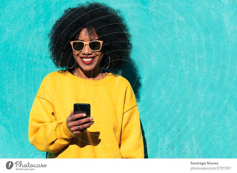 Schöne afroamerikanische Frau, die ein Handy auf der Straße benutzt. schwarz Afrikanisch Afro-Look Mensch Porträt PDA Jugendliche Mobile Telefon Mädchen