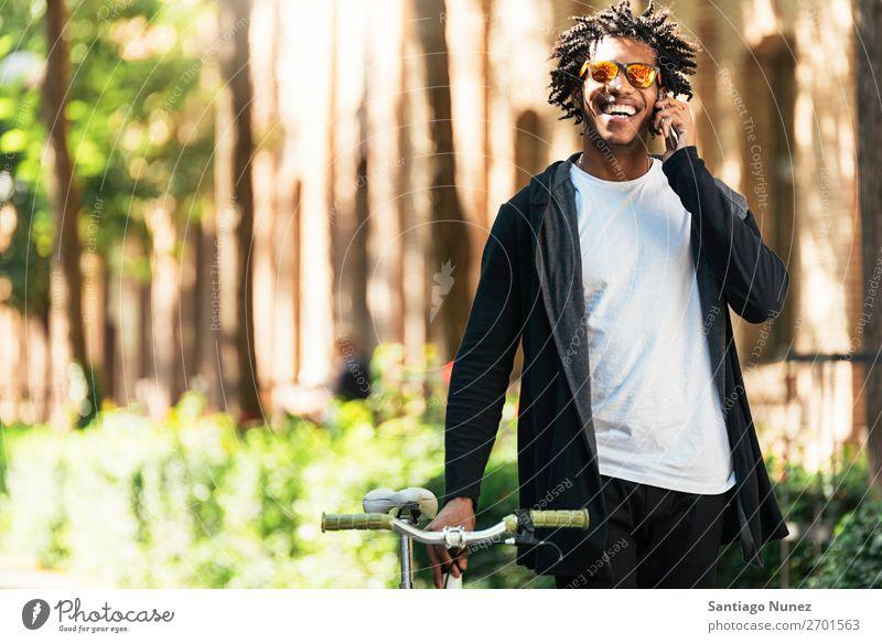 Afro-Jugendlicher benutzt Mobiltelefon und Fahrrad mit fester Gangschaltung Mann Afrikanisch schwarz Lifestyle attraktiv gutaussehend jung urban modern