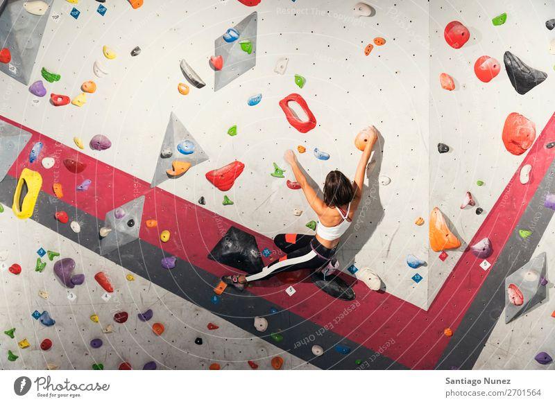 Frau, die das Klettern an einer künstlichen Wand in Innenräumen übt. Aufsteiger Felsen im Innenbereich Sporthalle Jugendliche Fitness Freizeit & Hobby Aktion