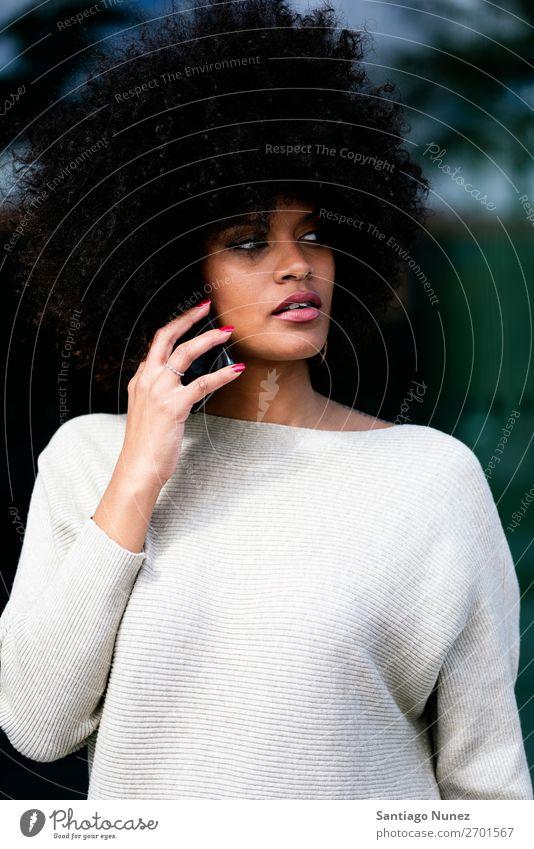 Porträt einer attraktiven Afrofrau mit Handy auf der Straße. Frau schwarz Afrikanisch Afro-Look Mensch Großstadt Jugendliche