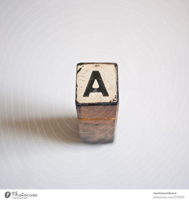 """Am Anfang ist das """"A"""" Stempel Zeichen Ziffern & Zahlen ästhetisch braun schwarz weiß authentisch Symmetrie Farbfoto Innenaufnahme Studioaufnahme Detailaufnahme"""