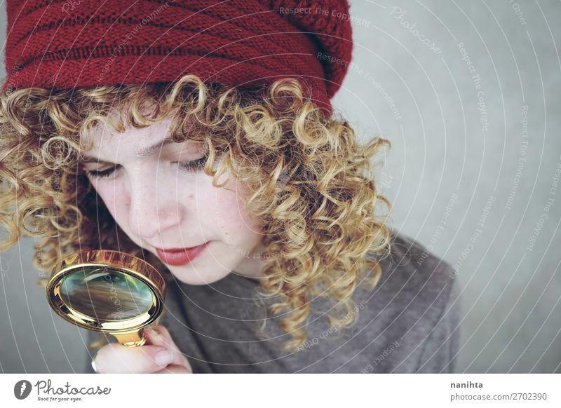 junge lustige Frau, die mit einer Lupe untersucht. Stil schön Gesicht Mensch feminin Junge Frau Jugendliche Erwachsene 1 18-30 Jahre Mode Hut blond Locken