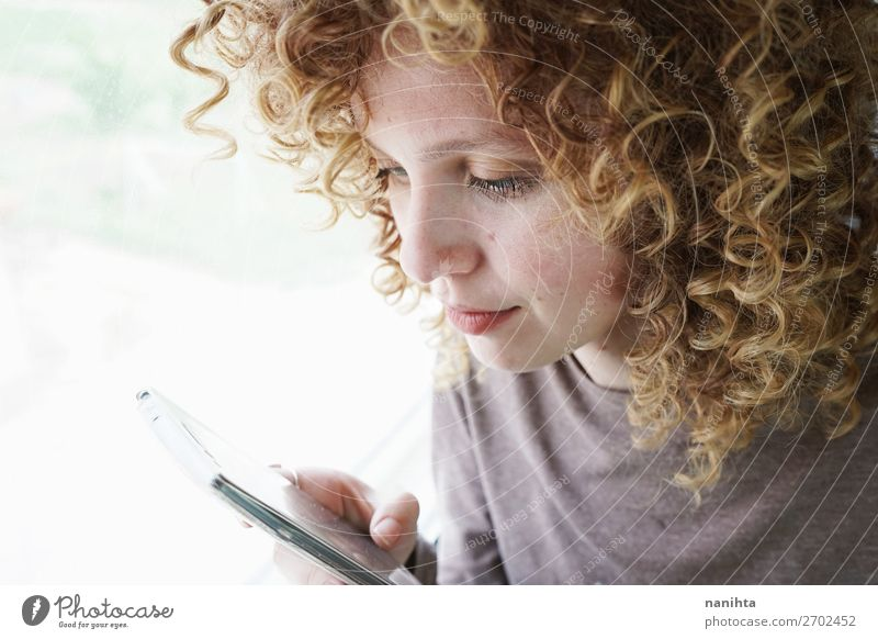 Porträt einer jungen Frau schaut auf ihr Smartphone. Stil schön Haare & Frisuren Haut Gesicht Telefon Handy PDA Technik & Technologie Unterhaltungselektronik