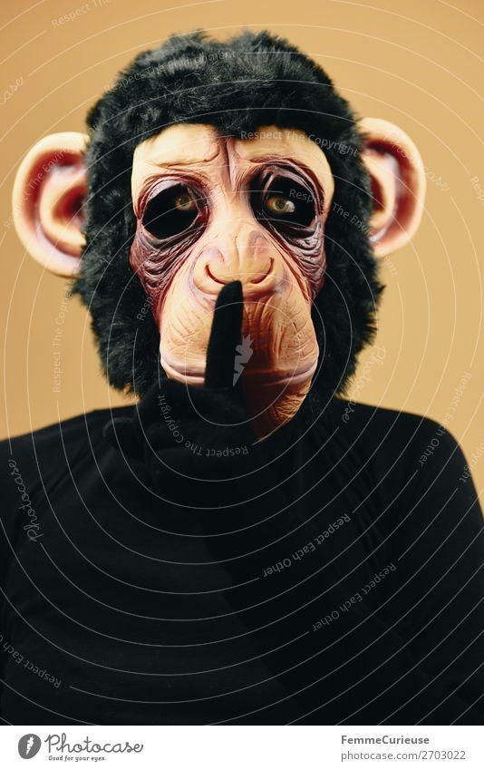 Person with monkey mask making psst gesture 1 Mensch Freude gestikulieren ruhig auffordern leise sein Maske Affen geheimnisvoll Schimpansen Karneval