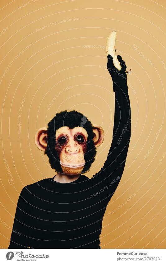 Person with monkey mask holding up a banana 1 Mensch Tier Freude Affen Schimpansen Kostüm Karneval Karnevalskostüm Karnevalsmaske verkleidet anonym verstecken