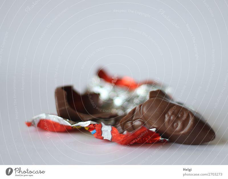 angeknabberter Schokoladenweihnachtsmann liegt auf dem Stanniolpapier Süßwaren Weihnachten & Advent Dekoration & Verzierung Verpackung Folie liegen authentisch
