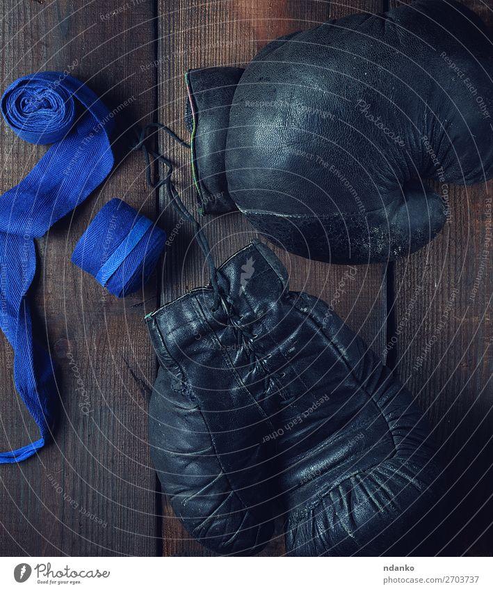 Paar sehr alte schwarze Boxhandschuhe aus Leder Lifestyle Fitness Sport Erfolg Seil Accessoire Ring Handschuhe Holz retro blau braun Schutz Konkurrenz Textil