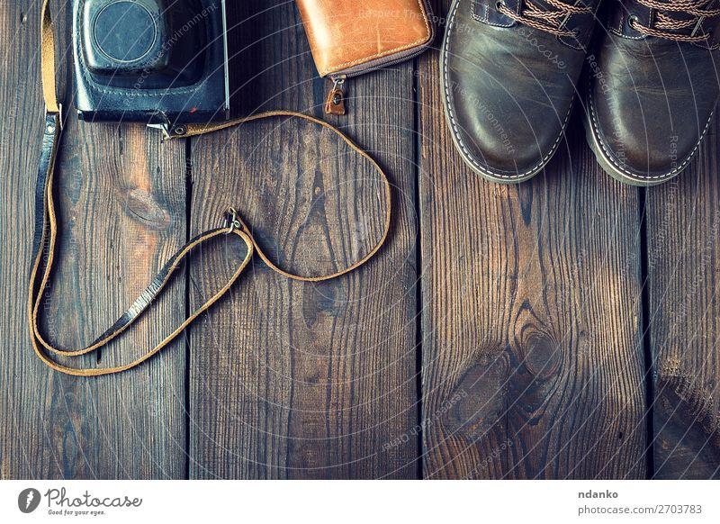 Paar lederne braune Schuhe und eine alte Vintage-Kamera. Stil Design Fotokamera Mode Bekleidung Leder Accessoire Holz retro schwarz Idee Hintergrund lässig