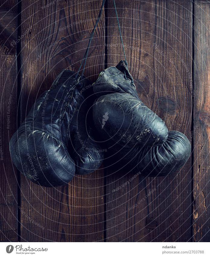 alte, schäbige, schwarze Boxhandschuhe aus Leder Lifestyle sportlich Sport Seil Handschuhe Holz Fitness hängen dreckig retro braun Schutz Konkurrenz gebraucht