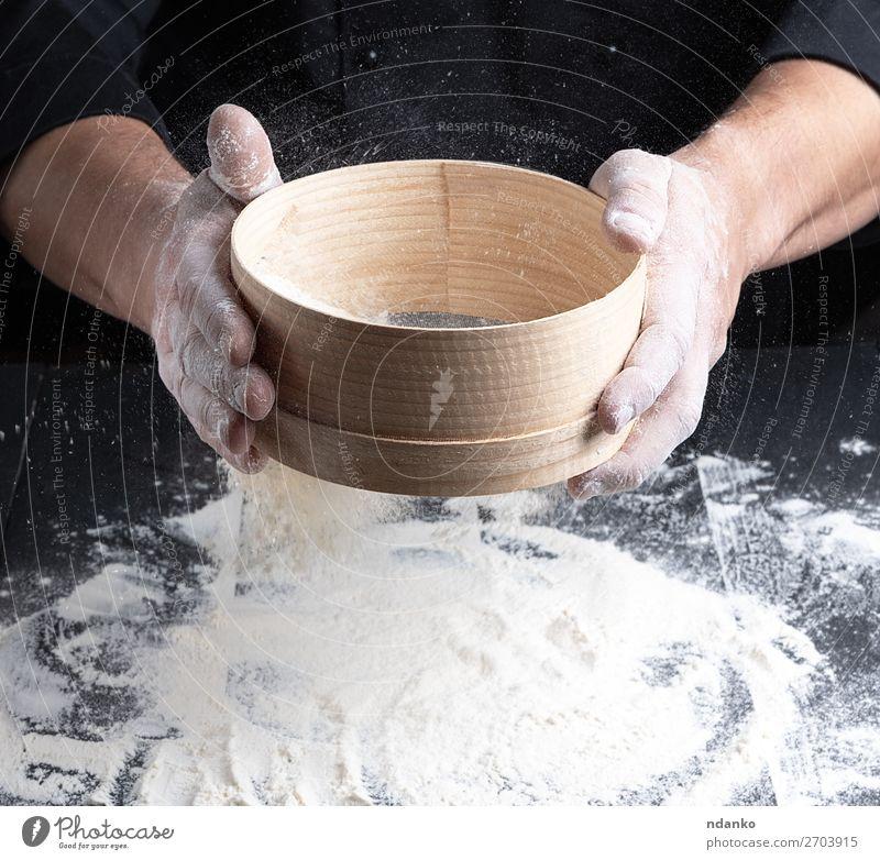 Koch in schwarzer Uniform hält in der Hand ein Sieb. Teigwaren Backwaren Brot Ernährung Tisch Küche Mensch Mann Erwachsene Holz Bewegung machen frisch weiß
