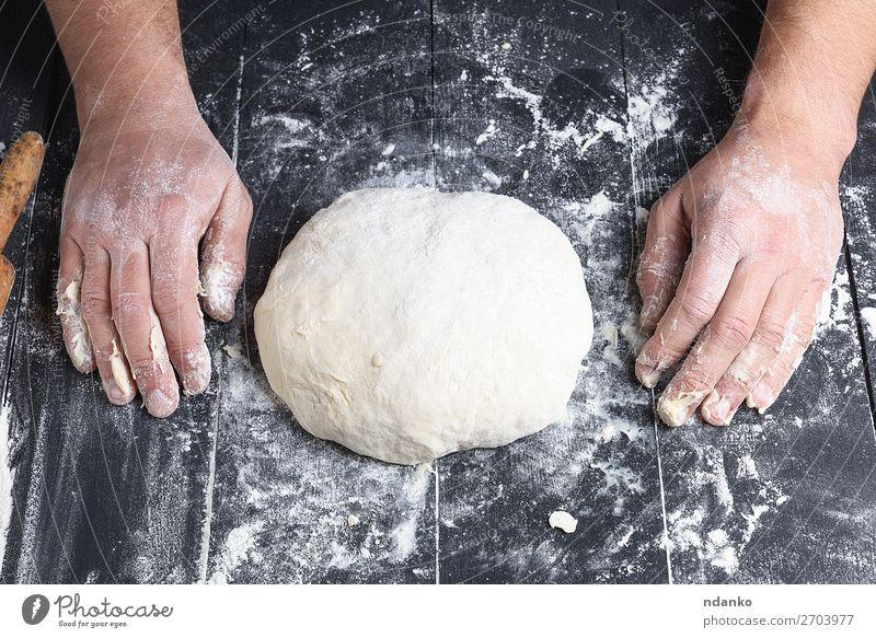 gekneteter Hefeteig aus Weizenweißmehl Teigwaren Backwaren Brot Ernährung Tisch Küche Koch Mensch Mann Erwachsene Hand Holz machen frisch schwarz Tradition