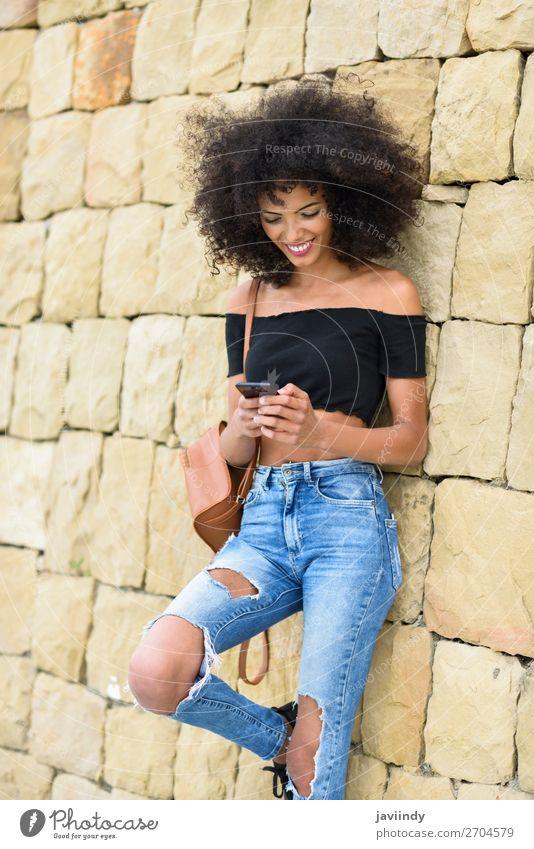 Lächelnde Frau, die ihr Smartphone im Freien ansieht. Lifestyle Stil Freude Glück schön Haare & Frisuren Telefon PDA Technik & Technologie Mensch feminin