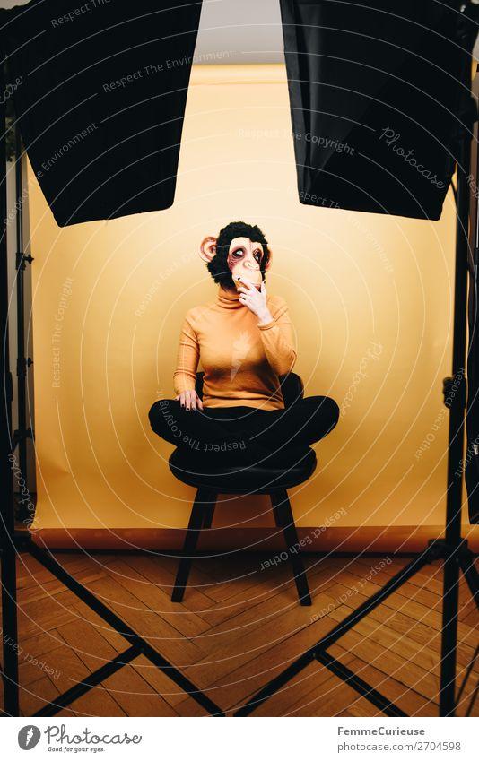 Woman with monkey mask sitting thoughtfully in photo studio feminin Frau Erwachsene 1 Mensch 18-30 Jahre Jugendliche 30-45 Jahre Freude Affen Affenmaske