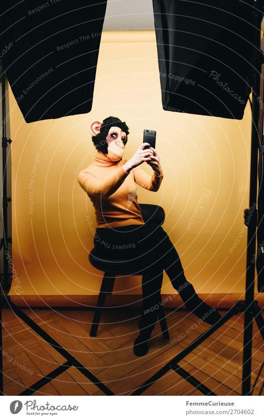 Woman with monkey mask making a selfie Frau Mensch Jugendliche 18-30 Jahre Erwachsene gelb feminin Kommunizieren Fotografie erleuchten Handy verstecken PDA