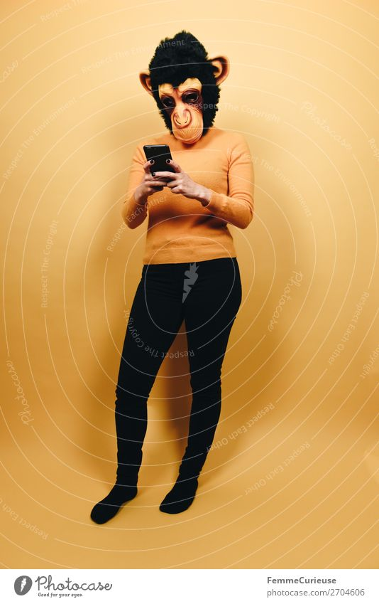 Woman with monkey mask looking at her smartphone Technik & Technologie Unterhaltungselektronik Telekommunikation feminin Frau Erwachsene 1 Mensch 18-30 Jahre