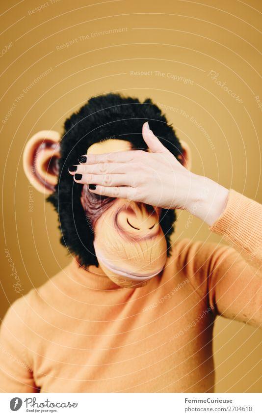 Woman with monkey mask holding her hand in front of her face feminin Frau Erwachsene 1 Mensch 18-30 Jahre Jugendliche 30-45 Jahre gelb Affen Schimpansen