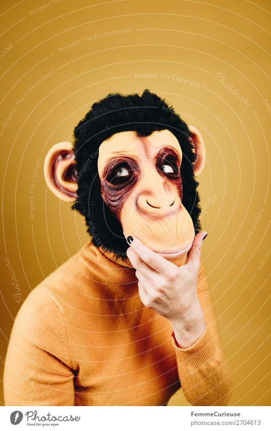Woman with monkey mask looking thoughtful feminin Frau Erwachsene 1 Mensch 18-30 Jahre Jugendliche 30-45 Jahre Freude Denken nachdenklich verträumt Evolution