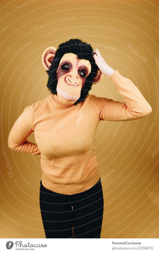 Woman with monkey mask scratching her head feminin Frau Erwachsene 1 Mensch 18-30 Jahre Jugendliche 30-45 Jahre Kommunizieren Evolution Menschlichkeit kratzen