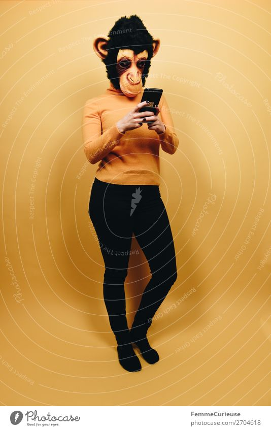 Woman with monkey mask looking at her smartphone Technik & Technologie Unterhaltungselektronik feminin Frau Erwachsene 1 Mensch 18-30 Jahre Jugendliche
