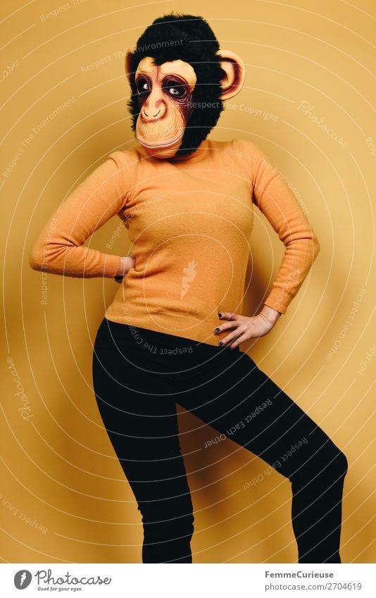 Woman with monkey mask posing against a yellow background feminin Frau Erwachsene 1 Mensch 18-30 Jahre Jugendliche 30-45 Jahre Freude Affen Schimpansen