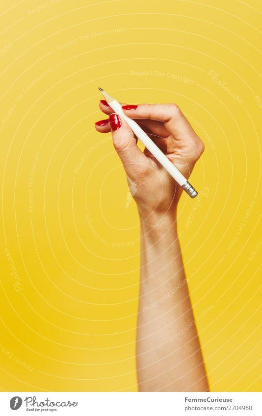 Forearm and hand with pencil against a yellow background feminin 1 Mensch Design gelb rot Nagellack Bleistift schreiben schreibend zeichnen Hand Finger Unterarm