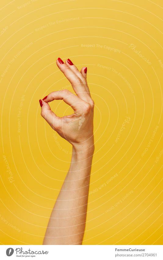 Hand signal for okay against a yellow background feminin 1 Mensch Zeichen Kommunizieren alles klar gestikulieren Finger Unterarm gelb rot Nagellack Rechtshänder