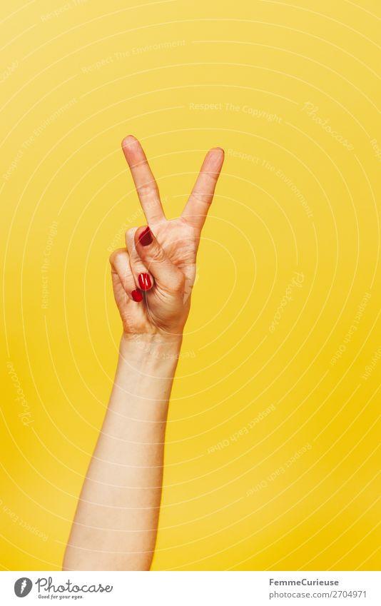 Hand signal for victory against a yellow background Frau Mensch Jugendliche rot 18-30 Jahre Erwachsene gelb feminin Glück Kommunizieren Erfolg Finger Zeichen