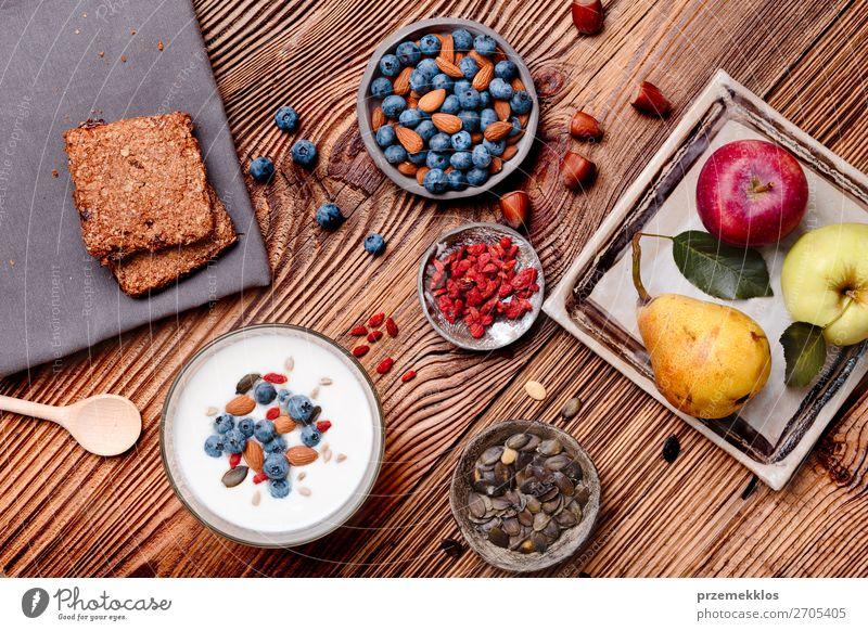 Frühstück auf dem Tisch. Joghurt mit Heidelbeer- und Mandelnzusatz Lebensmittel Milcherzeugnisse Frucht Apfel Getreide Brot Dessert Ernährung Essen Mittagessen