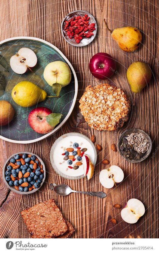 Frühstück auf dem Tisch. Joghurt mit Heidelbeer- und Mandelnzusatz Lebensmittel Milcherzeugnisse Frucht Apfel Brot Dessert Ernährung Essen Mittagessen