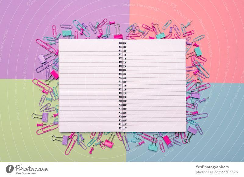 Offenes Notebook und bunte Büroartikel auf dem Schreibtisch Freude Beruf Arbeitsplatz Business Karriere Papier Fröhlichkeit blau grün rosa Farbe obere Ansicht