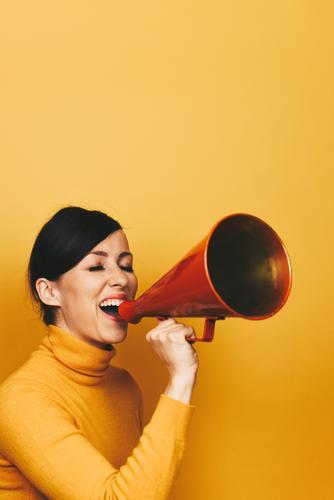 Woman making an announcement with a red megaphone feminin Frau Erwachsene 1 Mensch 18-30 Jahre Jugendliche 30-45 Jahre Kommunizieren Durchsage durchsagen