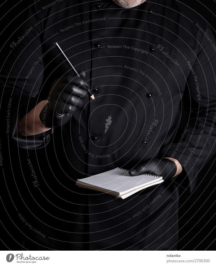 Koch in schwarzer Uniform und Handschuhen hält ein leeres Notizbuch. Küche Restaurant Arbeit & Erwerbstätigkeit Beruf Mensch Mann Erwachsene Bekleidung Hemd