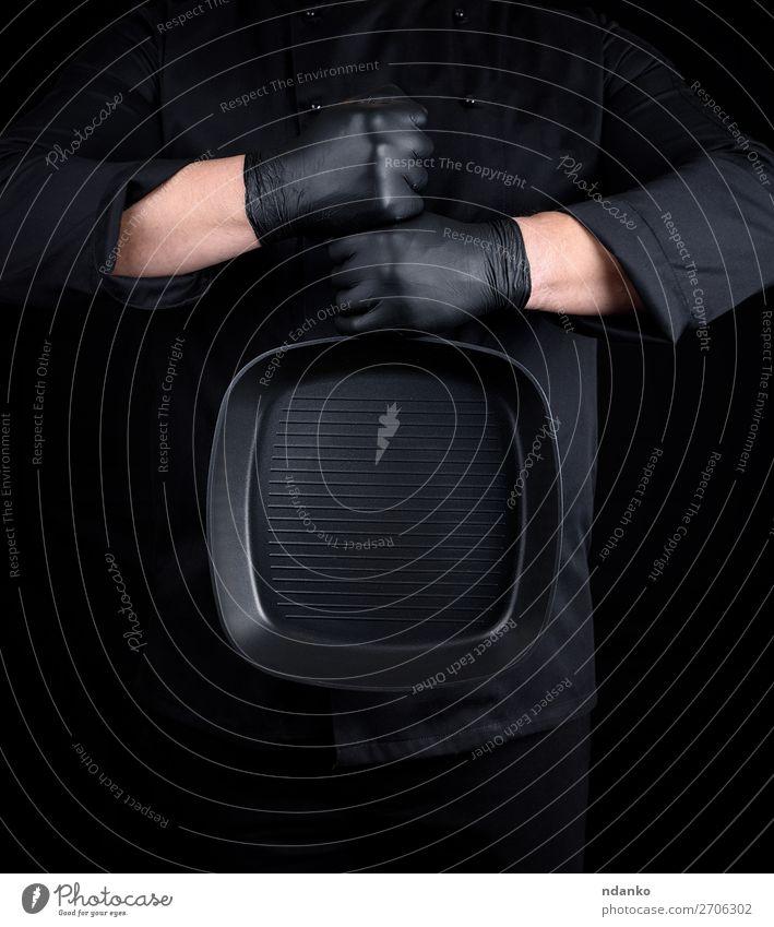 Koch in schwarzer Uniform und schwarzen Latexhandschuhen Pfanne Küche Restaurant Beruf Mensch Mann Erwachsene Hand Bekleidung Gußeisen Kaukasier Küchenchef