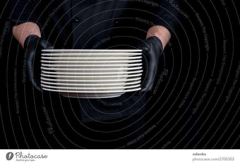 ein Stapel runder weißer leerer Teller Küche Restaurant Beruf Mensch Mann Erwachsene Hand Handschuhe stehen dunkel schwarz Kaukasier Küchenchef Koch