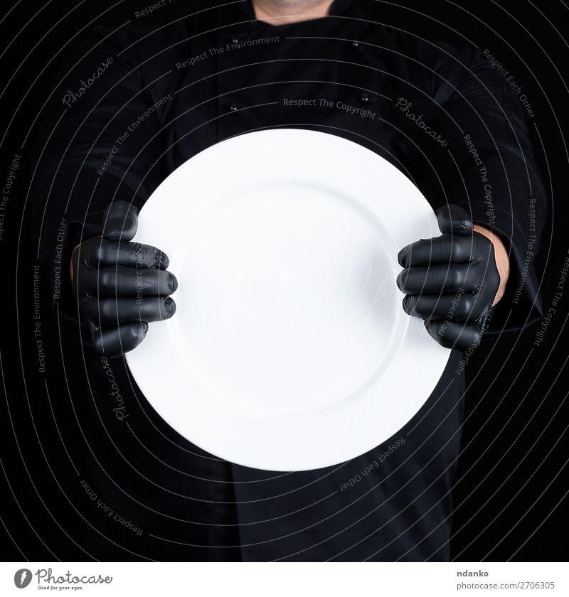 Koch in schwarzer Uniform mit einem runden leeren Teller. Küche Restaurant Beruf Mensch Mann Erwachsene Hand Handschuhe dunkel weiß Küchenchef Halt Lebensmittel