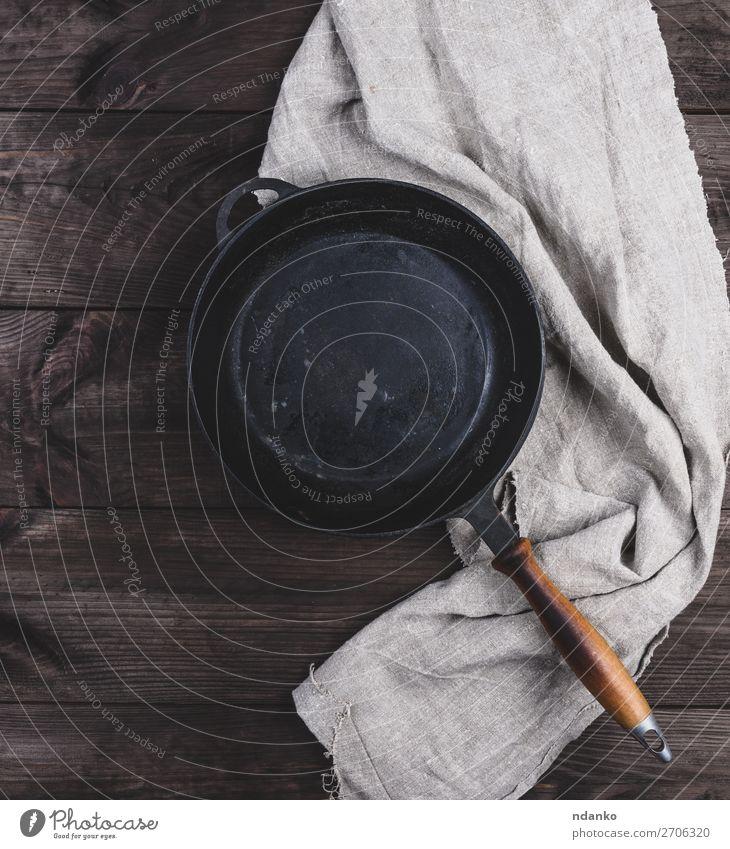 leere schwarze runde Bratpfanne mit Holzgriff Abendessen Pfanne Tisch Küche Metall alt dunkel oben Sauberkeit braun altehrwürdig Hintergrund Holzplatte gießen