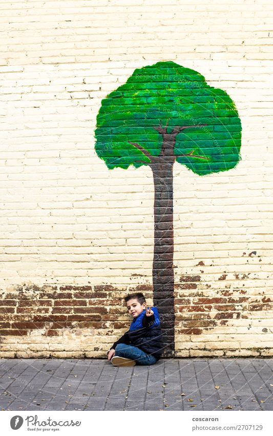 Kleines Kind, das unter einem Baum sitzt, der an einer Wand gemalt ist. Lifestyle Design Freude Glück schön Spielen Ferien & Urlaub & Reisen Abenteuer Winter