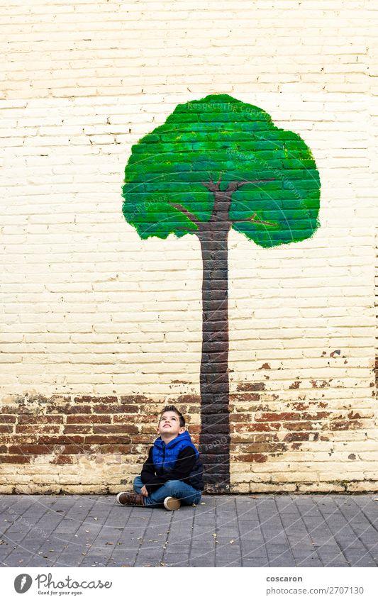 Kleines Kind, das unter einem Baum sitzt, der an einer Wand gemalt ist. Freude Glück schön Leben Spielen Abenteuer Sommer Winter Garten Hausbau Klettern