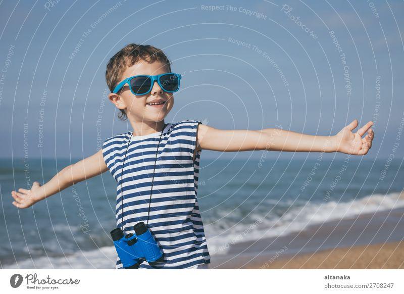 Ein glücklicher kleiner Junge, der tagsüber am Strand spielt. Er ist mit einer Matrosenweste bekleidet. Ein Kind, das sich draußen amüsiert. Konzept eines Matrosen im Urlaub.