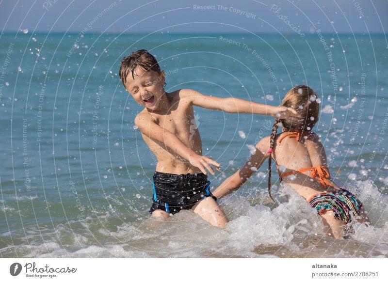 Glückliche Kinder, die tagsüber am Strand spielen. Zwei Kinder, die sich im Freien vergnügen. Konzept der Sommerferien und einer freundlichen Familie. Lifestyle