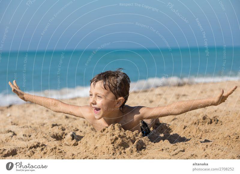 Ein glücklicher kleiner Junge, der tagsüber am Strand spielt. Ein Kind, das Spaß im Freien hat. Konzept des Urlaubs. Lifestyle Freude Glück schön Erholung