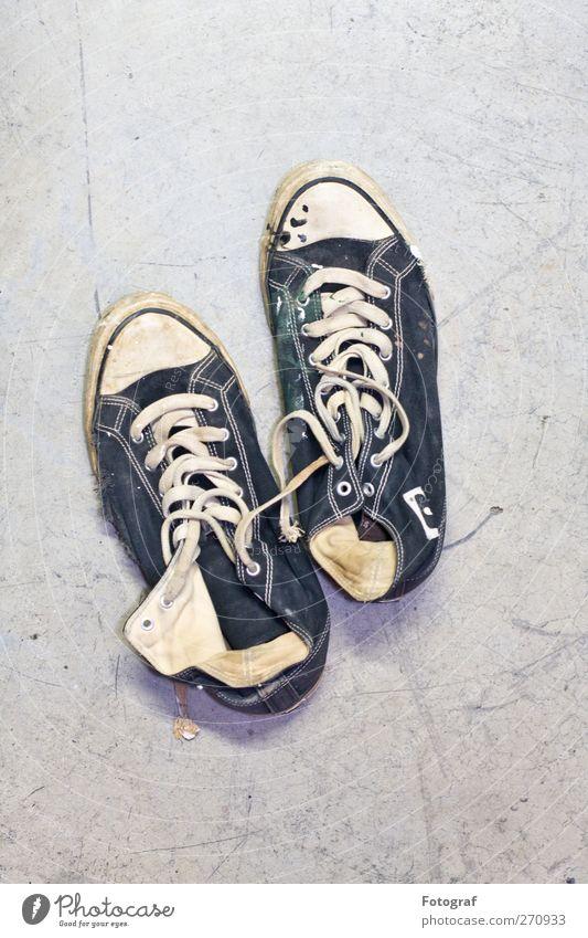 Treter. Schuhe Turnschuh blau schwarz weiß Chucks kaputt Schuhbänder Farbfoto Innenaufnahme Textfreiraum oben Hintergrund neutral Starke Tiefenschärfe